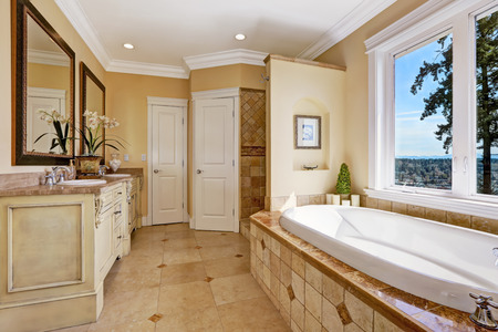 white wood floor: Soft tones bathroom interior with tile floor and tile wall trim, antique vanity with mirror and round bath tub in luxury house