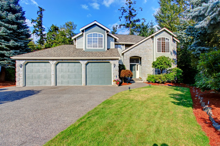 Luxury house exterior with three car garage and driveway 写真素材