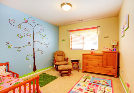 idea comfortable: Cheerful bright nursery room with contrast and painted wall. Stock Photo