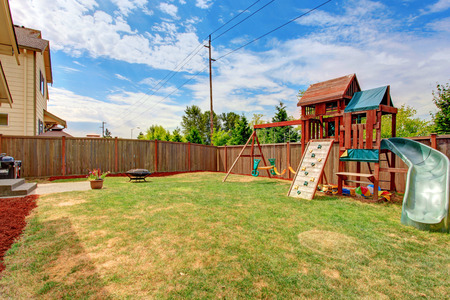 green back: Fenced backyard with patio area and playground for kids during sunny summer day