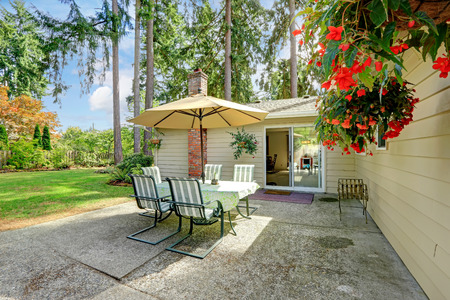 land slide: Countryside house exterior with small patio area  View of patio table set with umbrella