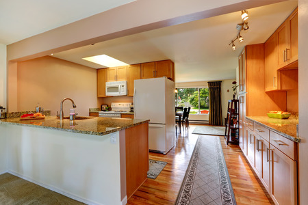 Kitchen room with white appliances and light tone cabinets. View of walk-through hallway with rug