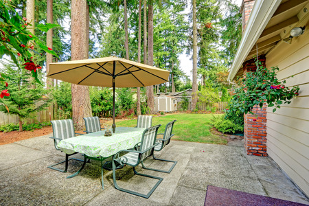 land slide: Countryside house exterior with small patio area. View of patio table set with umbrella