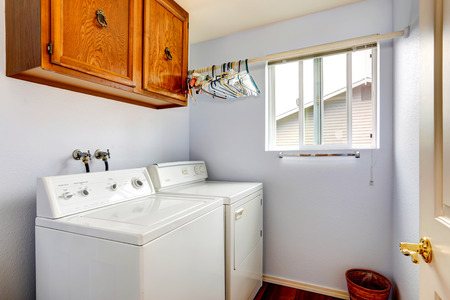 Simple laundry room with white appliances and wooden cabinet photo