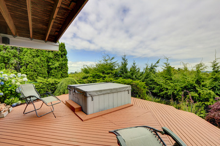 Cozy covered deck with jacuzzi and chairs. Deck has a beautiful nature view