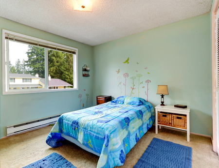 Aqua tones small bedroom interior with blue bed and rugs photo