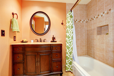 Warm bathroom interior. View of carved wood bathroom vanity cabinet with oval mirror