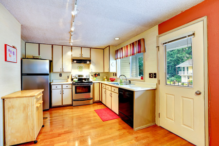 wood ceiling: Kitchen white cabinets with steel appliances and shiny hardwood floor