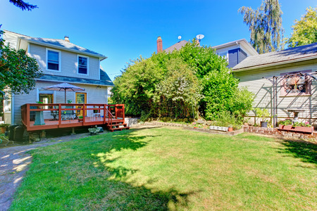 House exterior with walkout deck and patio area. View of large backyard land photo
