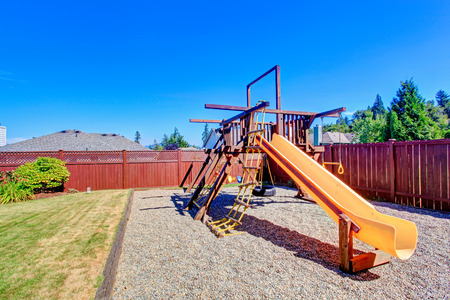 fenced: Fenced backyard with lawn and playground for kids.