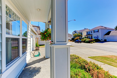 curb appeal: Entrance porch with columns decorated with hanging flower pot. View of driveway