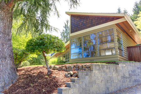 trim wall: Modern house exterior with glass wall and clapboard siding trim   View of front yard landscape Stock Photo