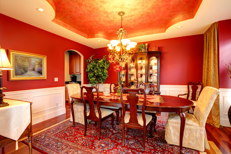 Luxury dining room with rich dining table  Bright red walls blend perfectly with designed ceiling photo