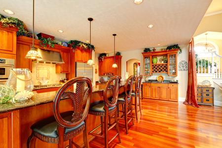 Bright luxury kitchen with rich carved wood stools and granite counter top photo