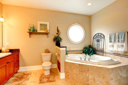 Luxury bathroom with round window and whirlpool tub