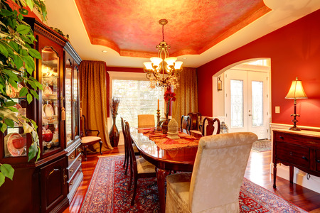 Luxury dining room with rich dining table. Bright red walls blend perfectly with designed ceiling