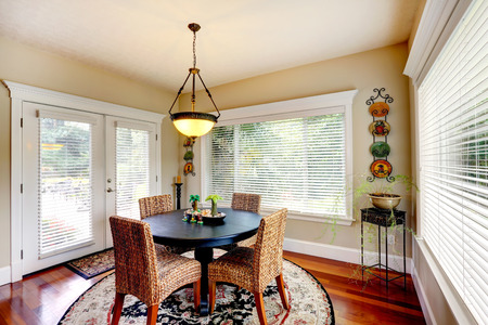 dining table and chairs: Bright room with round dining table and wicker chairs