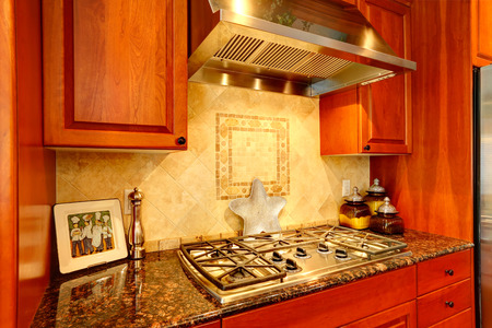 splash back: Kitchen cabinet with granite top and built-in stove. View of tile back splash trim Stock Photo