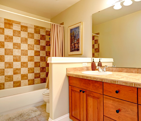 checker: Bathroom with checker board style wall trim and wooden vanity cabinet