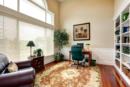 Hight ceiling office room interior furnished with small desk, leather armchair and wooden cabinet photo