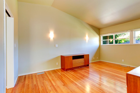 vaulted ceiling: Small empty room with hardwood floor and vaulted ceiling. Furnished with wooden cabinet