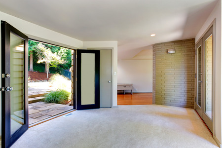 Empty house interior. Room with brick wall trim and carpet floor. View of open door to backyard