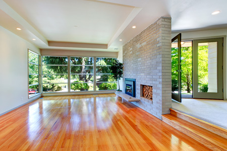 trim wall: Empty house interior. Living room with glass wall. View of brick wall with fireplace