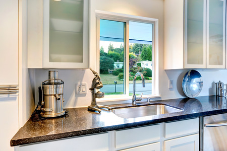 White kitchen cabinet with granite top ands sink. Bright kitchen room with window Banco de Imagens