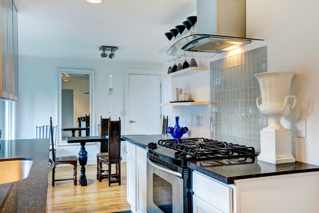dining table and chairs: White kitchen room with black granite tops. View of carved wood dining table with chairs Stock Photo