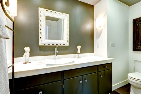 bathroom mirror: Bathroom in white and olive tones. View of dark wooden vanity cabinet with mirror