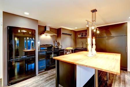 appliances: Modern kitchen interior in dark brown color with black appliances and kitchen island