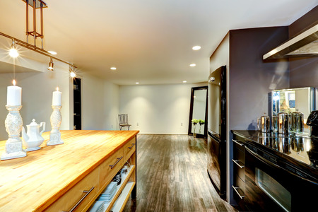 black appliances: Spacious kitchen room with black shiny appliances, wooden cabinet decorated with candles Stock Photo