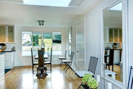 dining table and chairs: Bright white dining area with elegant wood carved table with chairs and big mirror Stock Photo