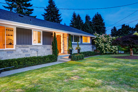 front house: Beautiful house exterior with lights on during warm summer evening