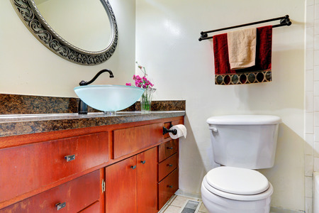 vessel sink: Bright bathroom vanity cabinet with vessel sink and granite top.