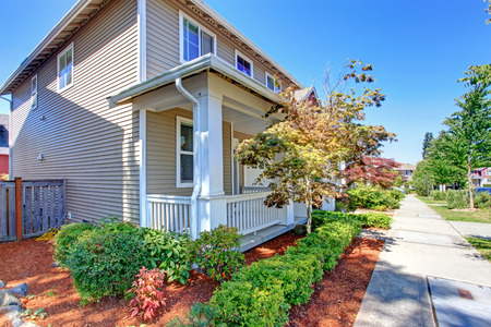 curb appeal: CLassic house entrance porch with columns and railings. View of flower bed and walkway Stock Photo