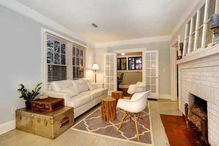 Living room wiht cozy fireplace. Furnished with antique chests and modern sofa and chairs photo