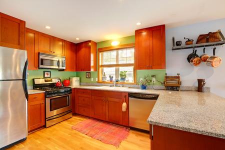 back kitchen: Kitchen interior with granite tops, green back splash and ss-appliances Stock Photo