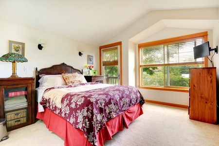 nightstands: Bedroom with vaulted ceiling and walkout deck. Big wood carved bed with nightstands Stock Photo