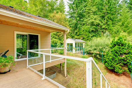 land slide: Walkout deck with glass railing. View of backyard with small shed