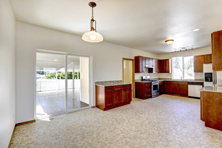 Bright kitchen interior with wooden cabinet, granite tops and steel appliances. Room has exit to walkout basement photo