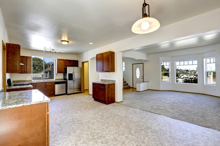 linoleum: House with open floor plan. Empty living and kitchen room with granite tops ans steel appliances