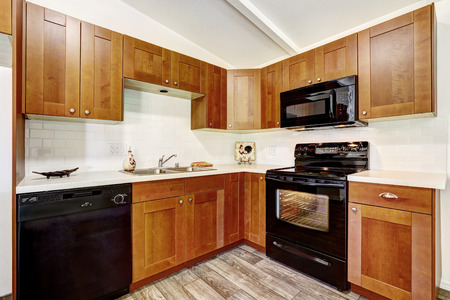 black appliances: Kitchen cabinets with black appliances and white tile wall trim