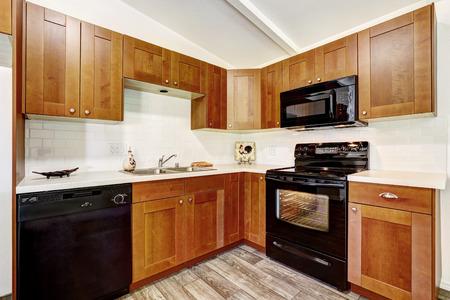 black appliances: Mobili da cucina con elettrodomestici neri e piastrelle bianche assetto muro