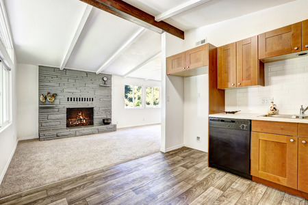 black appliances: Kitchen cabinets with black appliances and white tile wall trim. View of empty living room with fireplace