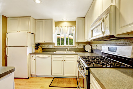 Simple white kitchen with steel stove and granite tops photo