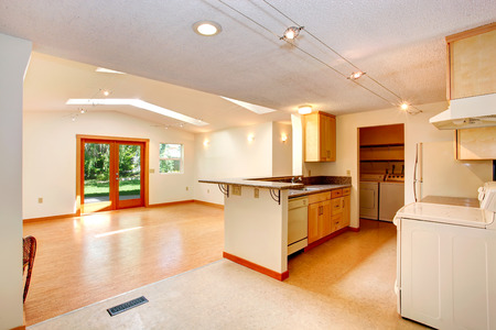 vaulted ceiling: Empty house interior with open floor plan. Living room with vaulted ceiling and skylights. View of kitchen area Stock Photo