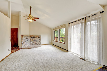 trim wall: Living room with vaulted ceiling in empty house. View of brick wall trim and brick base for stove