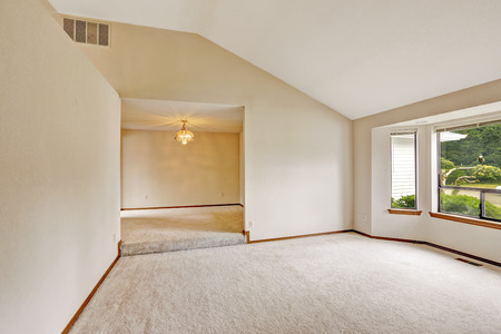 open floor plan: Empty house interior with open floor plan. Bright room with windows and soft ivory carpet floor