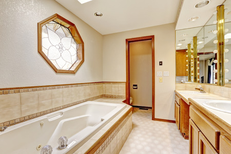 white trim: Ivory bathroom interior with miriror and tile wall trim. View of new bath tub Stock Photo